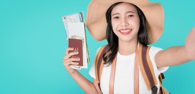 Sorriso felizmente viajante asiático da mulher que guarda o passaporte com bilhete e mapa, dinheiro.