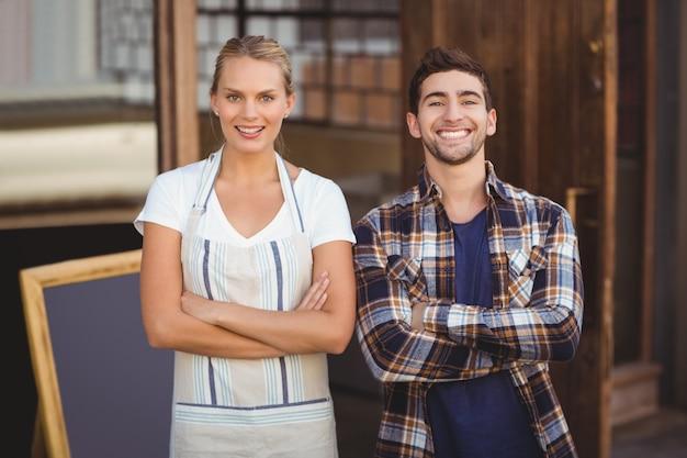 Sorriso garçonete e seu colega de braços cruzados
