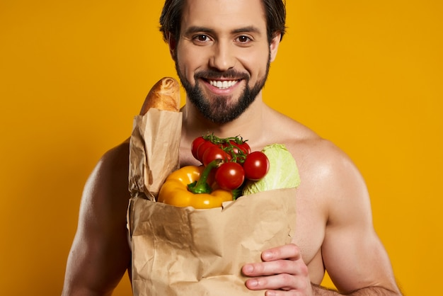 Sorriso homem detém saco de papel de legumes frescos