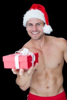 Sorriso homem musculoso posando em sexy santa traje oferecendo presente