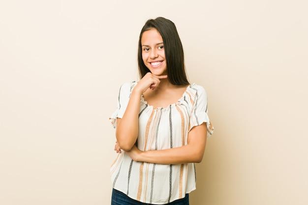 Sorriso latino-americano novo da mulher feliz e confiante, queixo tocante com mão.
