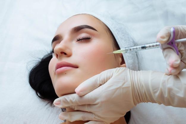 Sorriso, levantamento e mãos de médico esteticista de aumento de lábios fazendo procedimento de beleza para rosto feminino ...