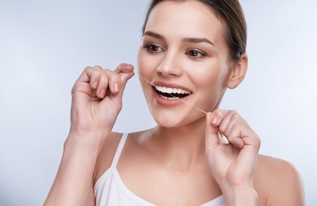Sorriso lindo, dentes brancos e fortes. cabeça e ombros de mulher com sorriso branco como a neve, segurando a linha do dente, conceito stomatological. garota limpando dente com linha