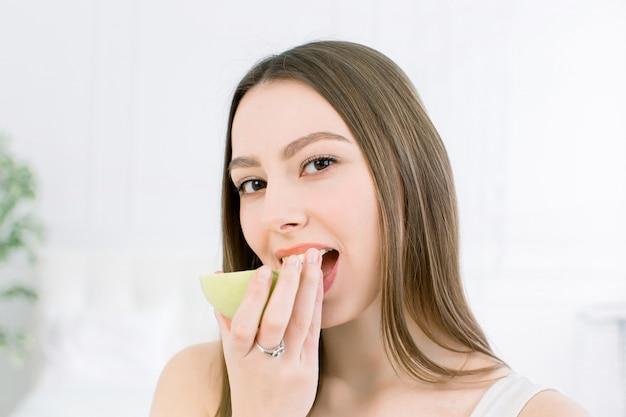 Sorriso lindo, dentes fortes e brancos. cabeça e ombros de jovem com sorriso branco como a neve segurando a maçã verde, tratamento de dentes.