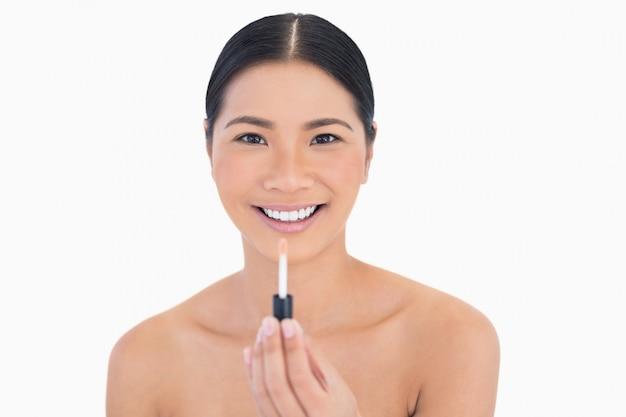 Sorriso modelo atraente segurando brilho labial