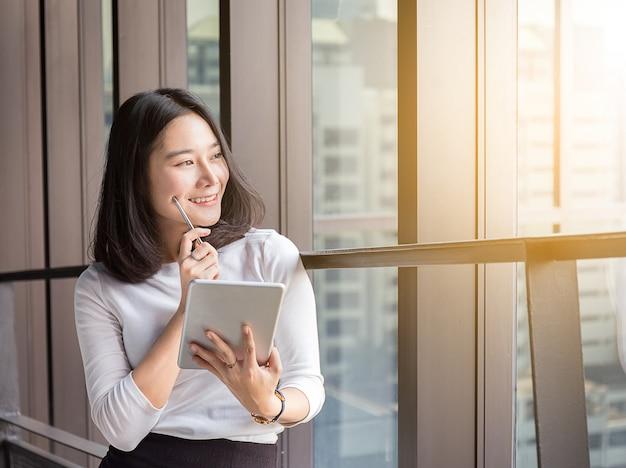 Sorriso mulher de negócios está pensando com tablet no escritório moderno