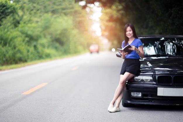 Sorriso mulher viajante em pé e lendo um livro com seu carro