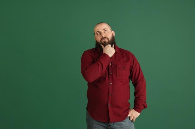 Sorriso. retrato de homem bonito caucasiano isolado na parede verde com copyspace. modelo masculino elegante com barba. conceito de emoções humanas, expressão facial, vendas, anúncio, moda, juventude.
