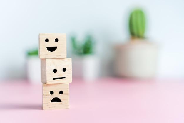 Sorriso rosto e carrinho ícone no cubo de madeira