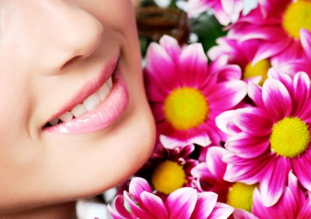 Sorriso saudável de menina com crisântemo rosa