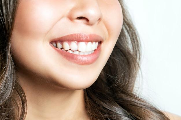 Sorriso saudável dos dentes de uma jovem mulher