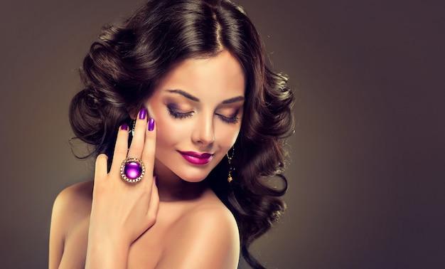 Sorriso suave no rosto de mulher jovem de cabelos negros com cabelos longos e volumosos com excelentes ondas. maquiagem, manicure e joias em tons roxos. beleza e charme.