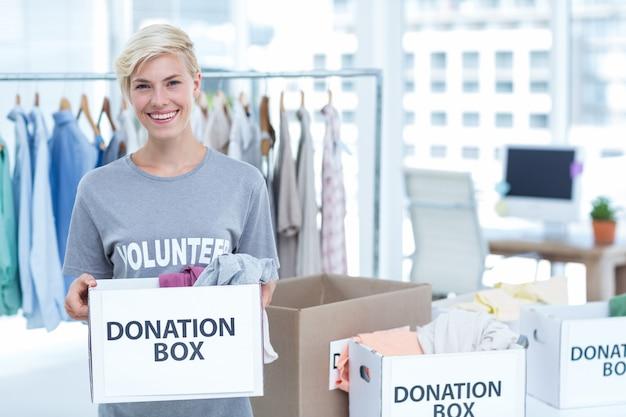 Sorriso voluntário segurando uma caixa de doações
