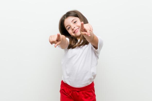 Sorrisos alegres da menina caucasiano apontando para a frente.