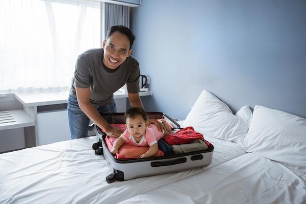 Sorrisos asiáticos pai segurando um bebê fofo deitado em uma mala aberta com olhando para a câmera