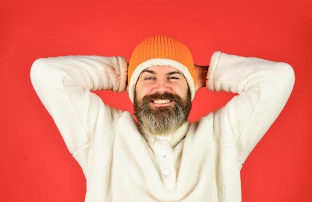 Sorrisos calorosos. barbudo homem usa chapéu de inverno. roupas da moda para o tempo frio. fundo vermelho moderno maduro. estilo de moda masculina. previsão do tempo no outono. gorro em malha protegida do frio.