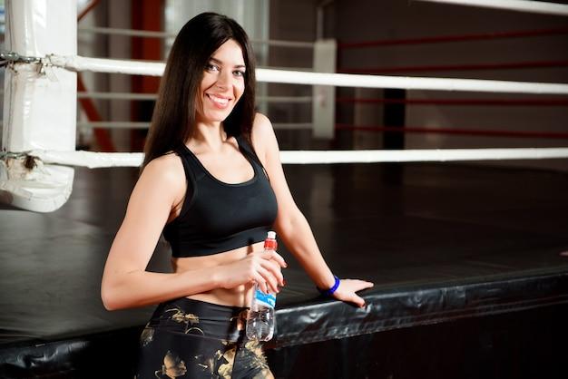 Sorrisos de esportes atraentes e água potável em pé na aula de fitness.