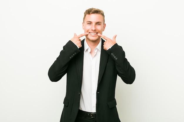 Sorrisos de homem de negócios caucasiano jovem, apontando os dedos na boca.