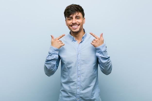 Sorrisos de homem de negócios latino-americanos jovens, apontando os dedos na boca.