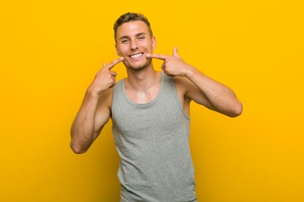 Sorrisos de homem jovem esporte caucasiano, apontando os dedos na boca.