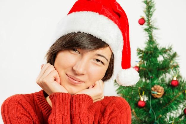 Sorrisos de mulher bonita em um chapéu de papai noel
