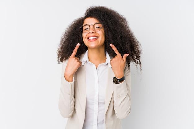 Sorrisos de mulher de negócios americano africano jovem, apontando os dedos na boca.