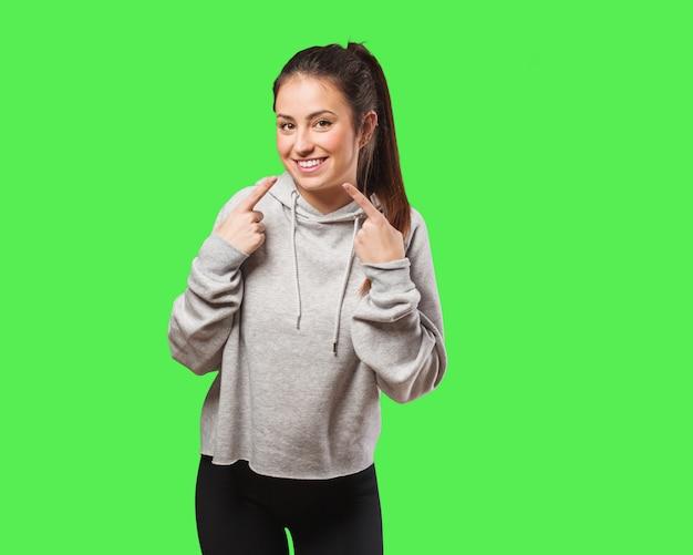 Sorrisos de mulher jovem fitness, apontando a boca