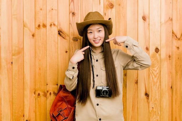 Sorrisos de mulher jovem viajante, apontando os dedos na boca
