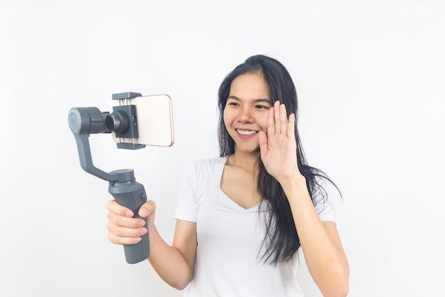 Sorrisos de mulher segurando cardan ou estabilizador com telefone móvel