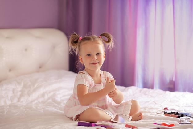Sorrisos loiros bonitinhos por três a quatro anos com um corte de cabelo sentado ao lado de um espelho com um conjunto de cosméticos e pincéis