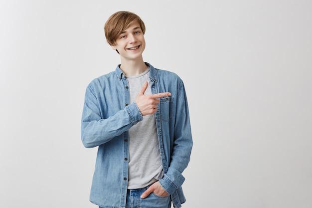 Sorrisos masculinos jovens caucasianos, indica no espaço da cópia, anuncia algo. homem feliz aponta com o dedo indicador, satisfez a expressão, sorri com aparelho. olhe aqui!