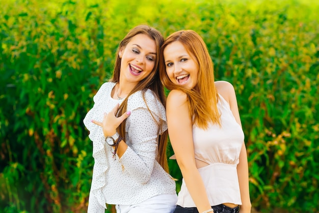 Sorrisos sinceros dos melhores amigos que posam um fotógrafo no fundo de uma grama alta