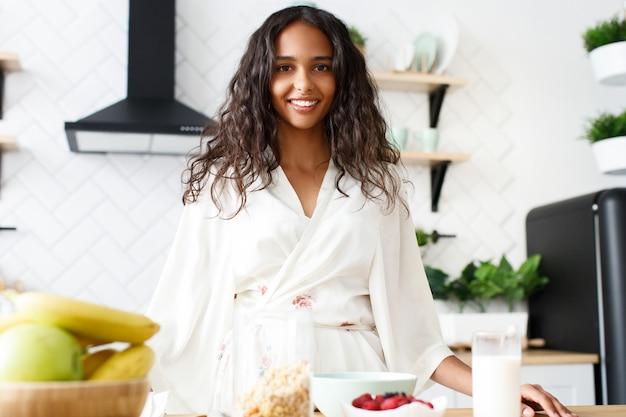 Sorriu atraente mulata está de pé perto da mesa cheia de alimentos saudáveis na cozinha moderna branca, vestida com roupas de dormir com cabelos soltos e olhando em linha reta
