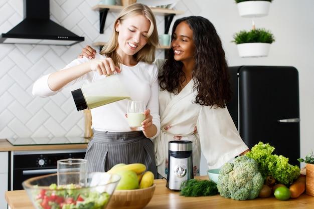 Sorriu mulata atraente em pijamas e mulher caucasiana com smoothie saudável está de pé perto da mesa cheia de frutas e legumes frescos na cozinha moderna branca