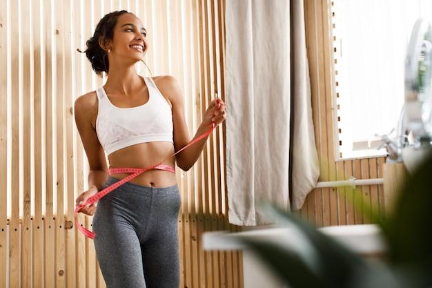 Sorriu mulata atraente mulher com fita de centímetro na cintura em sportswear indoor