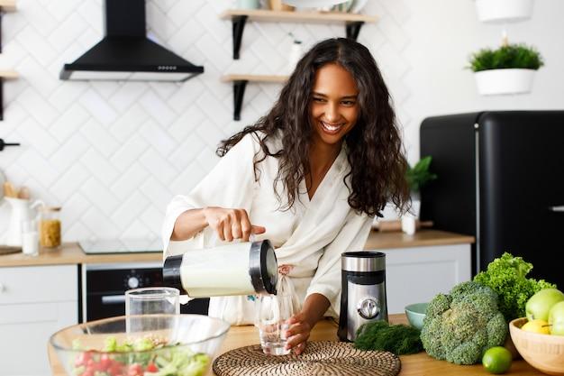 Sorriu mulata bonita está derramando smoothie verde sobre o glasswear perto da mesa com legumes frescos na cozinha moderna branca, vestida em roupas de dormir com cabelos soltos