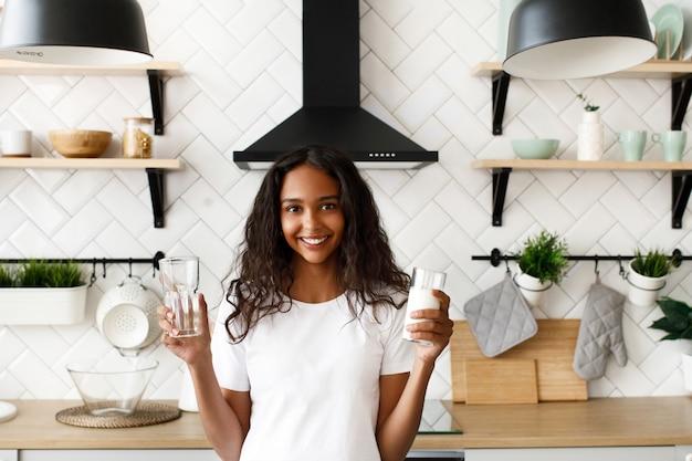 Sorriu mulata com cabelo solto está segurando o copo vazio e copo com leite perto da mesa da cozinha na moderna cozinha branca, vestida com camiseta branca