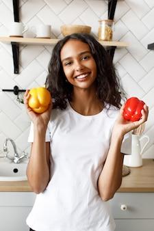 Sorriu mulata vestida com camiseta branca, com rosto bonito e cabelo solto está segurando pimentões amarelos e vermelhos nas mãos na cozinha