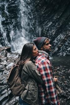 Sorte de ter um ao outro. lindo casal jovem se abraçando em pé perto da cachoeira