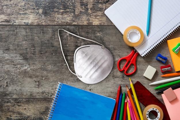 Sortidas de material escolar e máscara protetora na mesa de madeira voltar ao conceito de escola