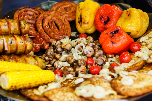 Sortidas deliciosas carnes grelhadas com legumes sobre as brasas em um churrasco