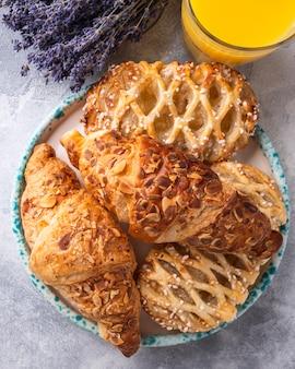 Sortido de bolos frescos e croissants em um suco de laranja de placa. vista do topo.