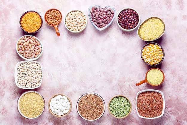 Sortido de leguminosas e feijões em diferentes tigelas em pedra clara. vista do topo. alimentos saudáveis de proteína vegana.