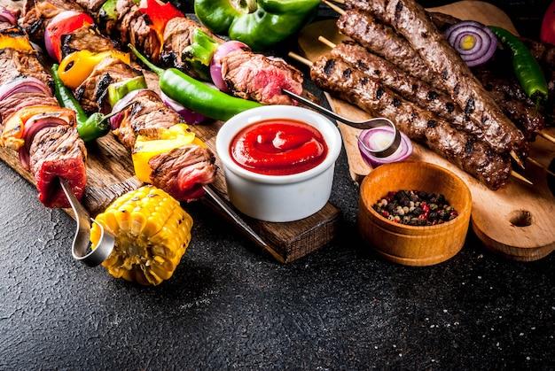 Sortido de várias churrasqueiras, churrasqueiras, salsichas, filé de carne grelhada, legumes frescos, molhos, especiarias, mesa de concreto enferrujado escuro, acima do espaço da cópia