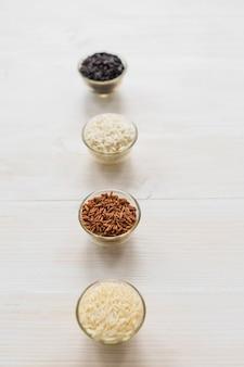 Sortido, variedade, arroz cru, em, tigela vidro, organizado, em, fila, ligado, tabela madeira