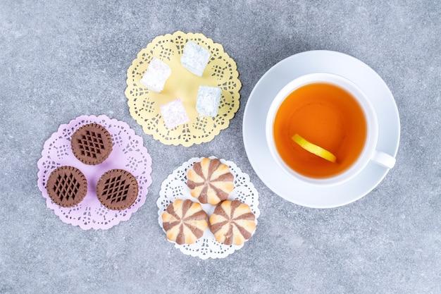 Sortidos de doces e chávenas de chá na superfície de mármore