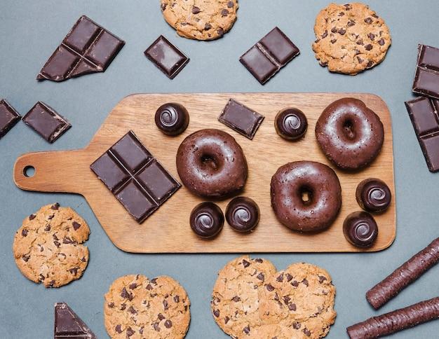 Sortimento de leigos plana com donuts na tábua de corte