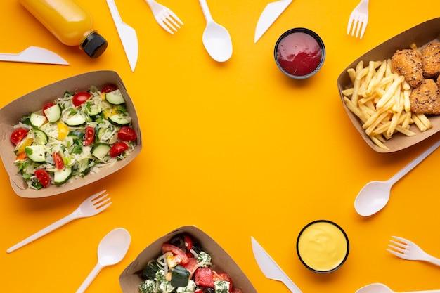 Sortimento de leigos plana com moldura de comida e utensílios de mesa