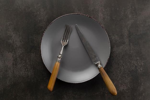 Sortimento de mesa com prato e talheres plano