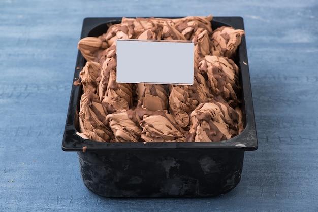 Sorvete apetitoso em um recipiente de plástico com etiqueta de preço em um fundo azul decorativo